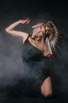 Идеальная женщина в одежде американских индейцев в дыму на сером фоне. шапка из перьев. загадочный мистический образ, сексуальное тело, красивая спина. привлекательная блондинка с красивым лицом