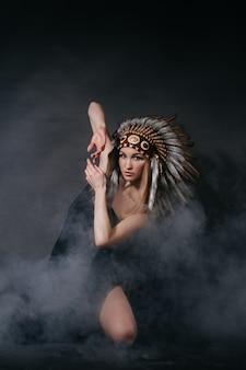 灰色の背景に煙の中のアメリカインディアンの衣装を着た完璧な女性。羽で作った帽子。神秘的な神秘的な方法