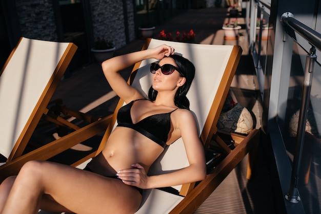 スイミングプールの日焼けの近くの完璧な女性。日光浴をしている若い美しい少女