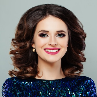 Perfect woman with cute smile and makeup. smiling model with curly hairstyle and evening make-up