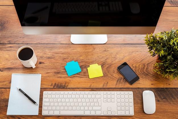 Идеальное рабочее место. вид сверху удобного рабочего места с деревянным столом и компьютером, стоящим на нем