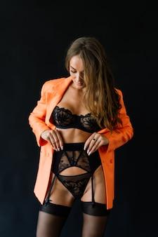 魅惑的な黒のランジェリーとストッキング、スタジオショットで完璧な若い美しさの女性