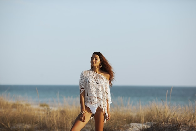 Perfect young boho woman standing on a sandy tropical beach against beautiful bokeh copy space