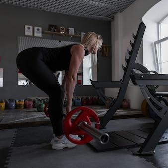 스포티 한 몸매를 가진 완벽한 젊은 여성이 체육관에서 바벨로 운동을하고 있습니다.