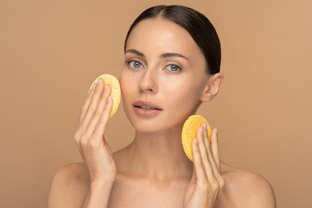 누드 메이크업과 벌거 벗은 어깨가 그녀의 얼굴을 청소하는 완벽한 젊은 여성