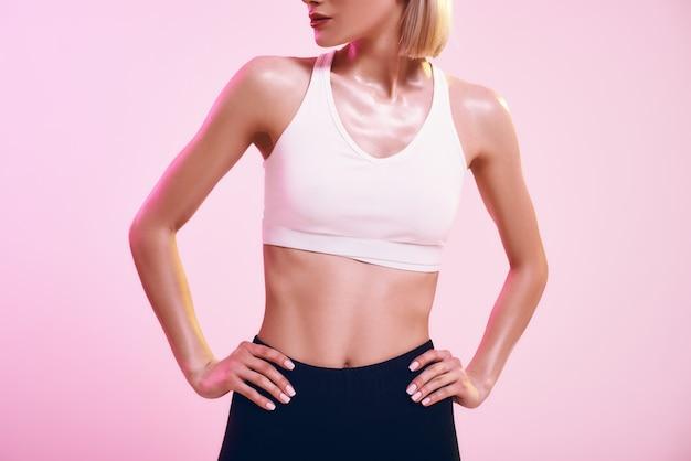 분홍색에 맞서 서 있는 운동복을 입은 이상적인 몸매를 가진 스포티한 날씬한 여성의 완벽하게 자른 사진