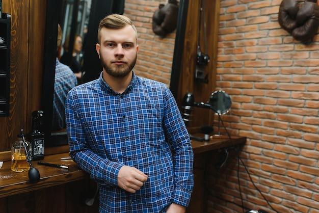 Совершенство. красивый бородатый мужчина в парикмахерской. портрет стильного молодого парня в куртке, касаясь его волос во время посещения парикмахерской или салона.