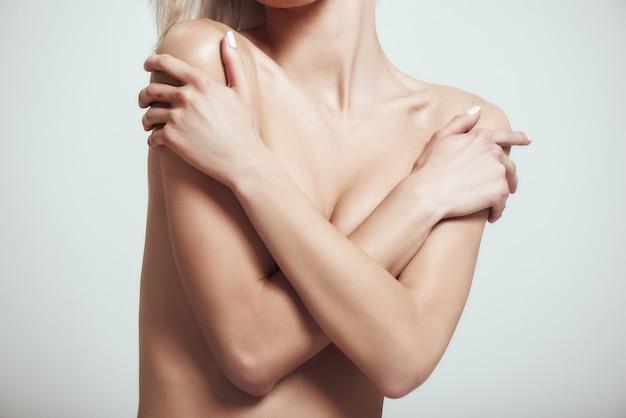 彼女の胸を彼女で覆っているセクシーなスリムな女性の人体トリミング写真の完璧さ