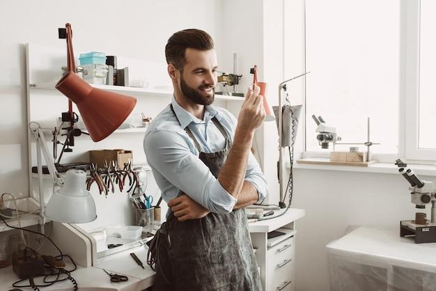 완전. 작업장에 서서 반지를 보고 검사하는 젊고 웃는 남성 보석상의 초상화. 사업. 보석 장비. 부속품