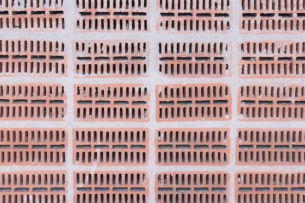Perforated brick wall background. construction texture