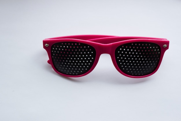 Perforated glasses pink glasses on a white background glasses for improving vision