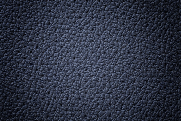 Perforated navy blue leather texture background, closeup. denim backdrop from wrinkle skin.