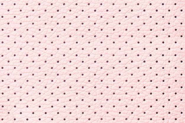 Perforated pink leather texture background, closeup