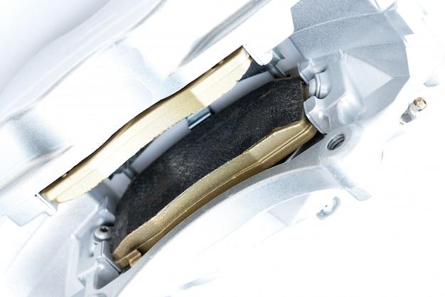 Performance braking system,  close up of new brake pads in silver racing brake caliper.