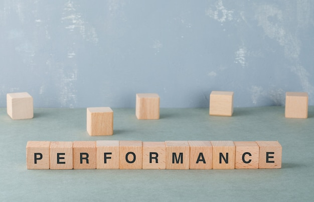 Performance and business concept with wooden blocks with words on it side view.