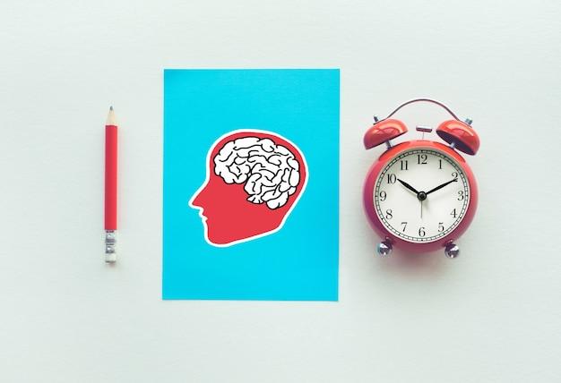 鉛筆と脳のサインの描画と白い背景の目覚まし時計とパフォーマンスの概念。時間と日付行。上面図の画像