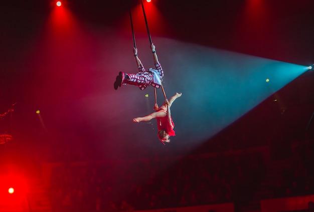 Выступление воздушных артистов на цирковой арене.