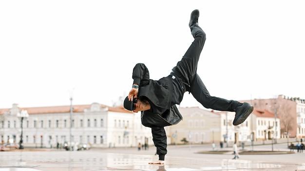 Исполнение танца молодого стильного парня в черной одежде