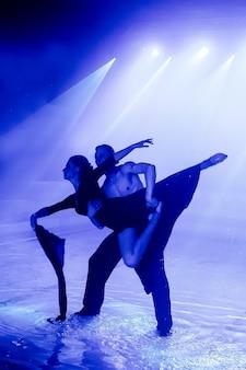 クラブライトを背景にしたダンスグループの水上パフォーマンス。