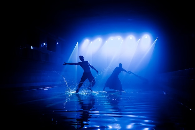 Performance on the water of a dance group against the background of club light.