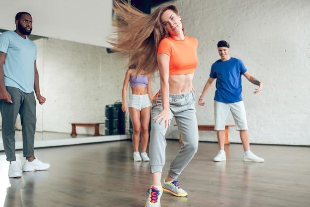 舞台芸術。ダンスの動きでカジュアルな服を着たかわいい細い長髪の女の子