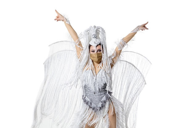 Performing. beautiful young woman in carnival masquerade costume with white feathers dancing on white background. concept of holidays celebration, festive time, dance, party, happiness. copyspace