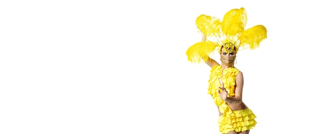 Performing. beautiful young woman in carnival masquerade costume with yellow feathers dancing on white background. concept of holidays celebration, festive time, dance, party, happiness. copyspace