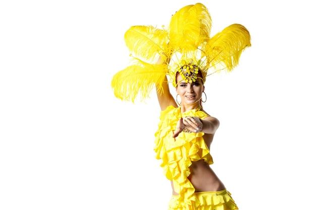 실행할 수 있는. 흰색 바탕에 춤추는 노란 깃털을 가진 카니발 무도회 의상에서 아름 다운 젊은 여자. 휴일 축하, 축제 시간, 댄스, 파티, 행복의 개념. copyspace