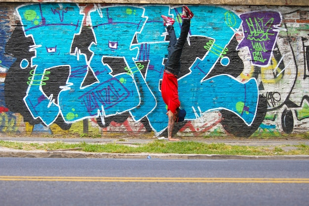 A performing hiphop dancer in front of a graffiti wall.