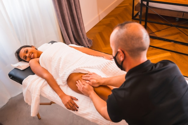 Performing a massage at home satisfied client on the legs