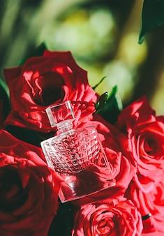 高級ギフトの美しさのフラットレイの背景と化粧品のプロとしての赤いバラの香水の香水と花束...
