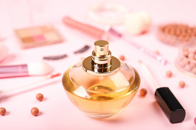분홍색 배경에 향수 및 장식 화장품.