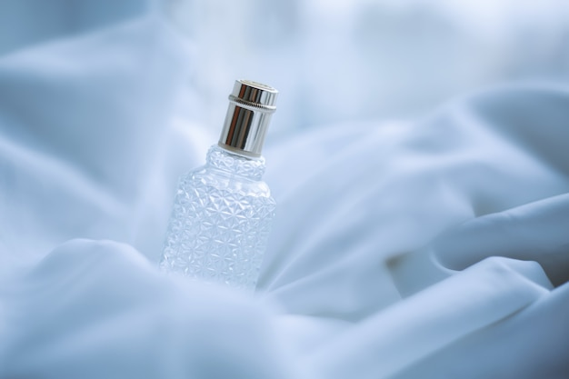 Perfume on a background of white fabric in waves