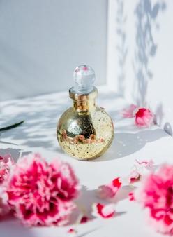 白い壁の周りに香水瓶とナデシコの花