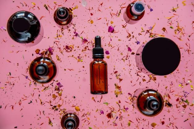 향수병 및 건조 꽃 주위에 분홍색 표면