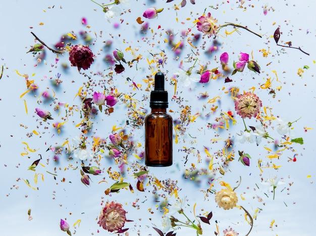 향수 병 및 흰색 표면 주위에 마른 꽃