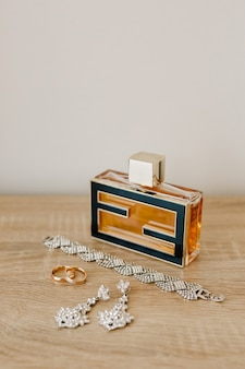 A perfume bottle, a bracelet, earrings-studs and wedding rings on a wooden table against a light wall