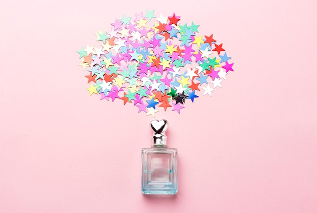 Perfume bottle and confetti on pink background, flat lay