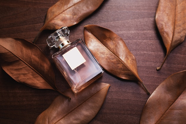 Perfume bottle and dry brown leaves