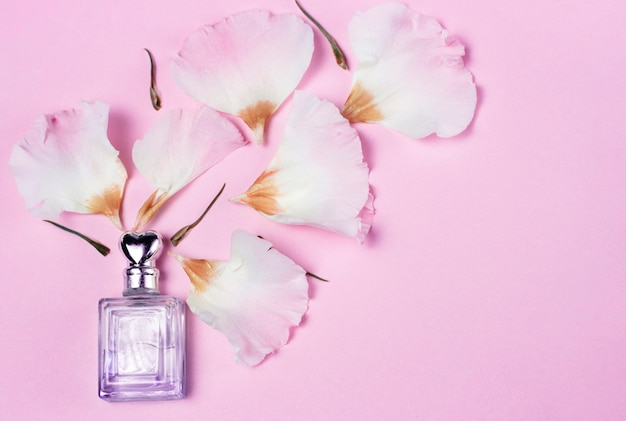 Perfume bottle and flower petals on pink background, top view