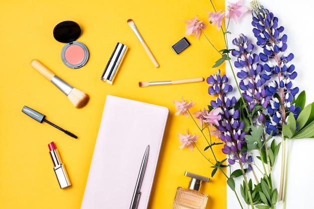 香水瓶、花、化粧品、黄色の背景にメモ帳を構成します。