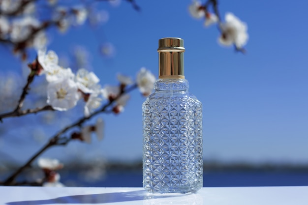 Perfume bottle and flowers on nature