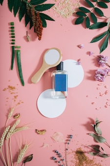 Perfume bottle in flowers on pink wall with white circle shape and mirror. spring wall with aroma perfume. flat lay