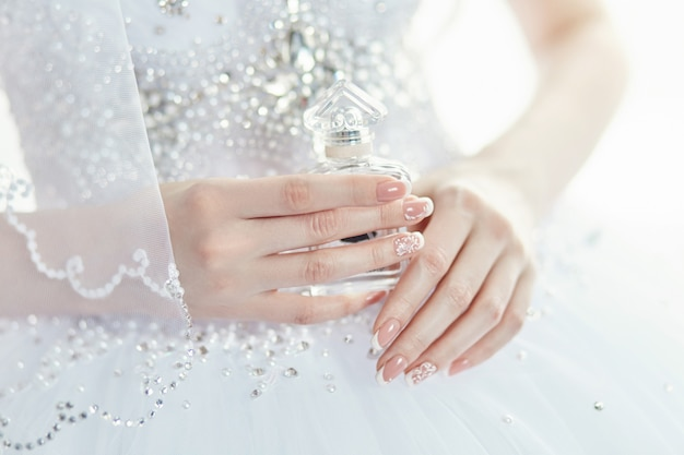 Perfume bottle in the hands of the bride