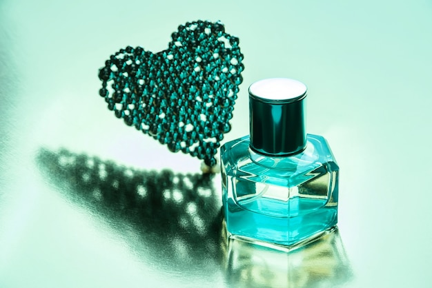 Perfume bottle and heart-shaped decoration on a light surface.
