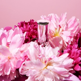 Флакон духов перед розовыми пионами