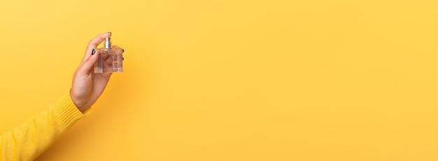 노란색 배경 위에 손에 향수 병, 파노라마 모의