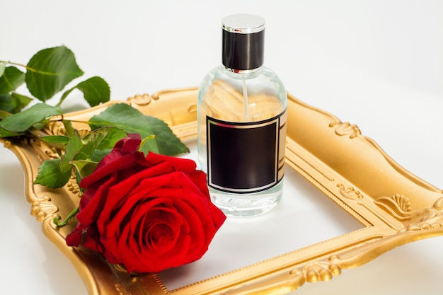 Perfume in a bottle is decorated with a red rose and a gold frame, isolated on a white wall. concept aromatherapy photo for advertising in the perfume industry.