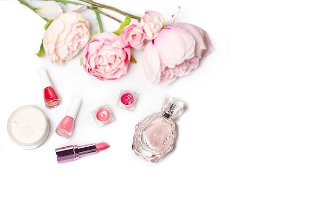香水瓶、マニキュア、口紅。ファッション女性の静物。白い表面に花で女性のものをポップ
