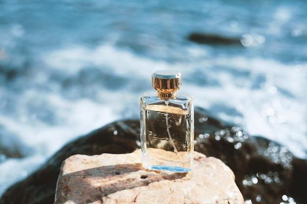 青い海の背景に香水瓶